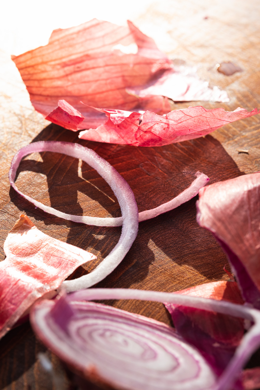 red onion slices and skin on a wooden end-grain cutting board