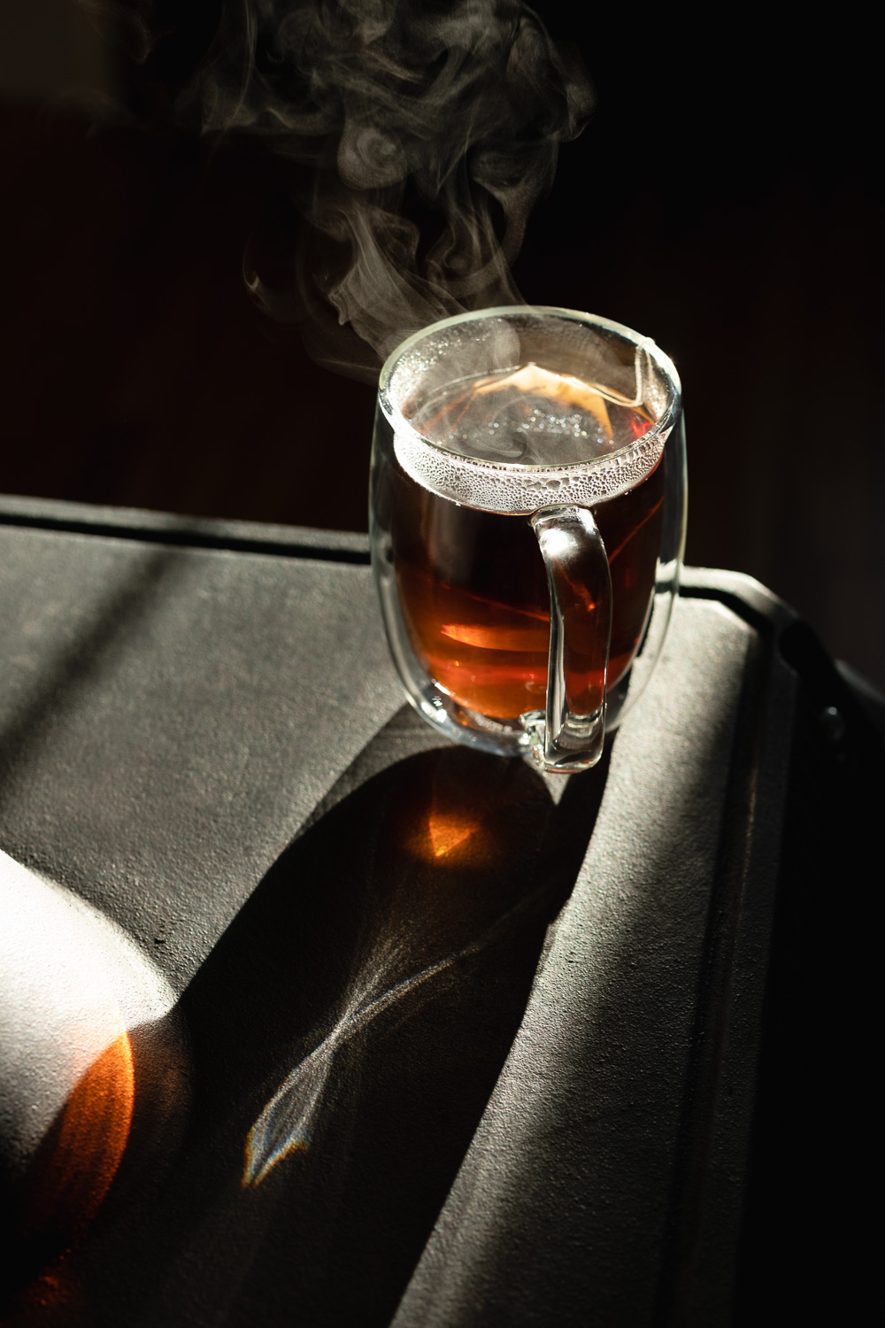 steaming tea in a glass mug in the afternoon sunlight